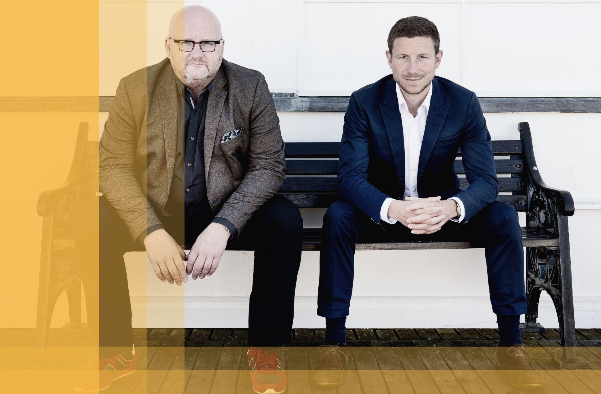 Mark und Lars sitzen auf einer Bank und blicken in die Kamera
