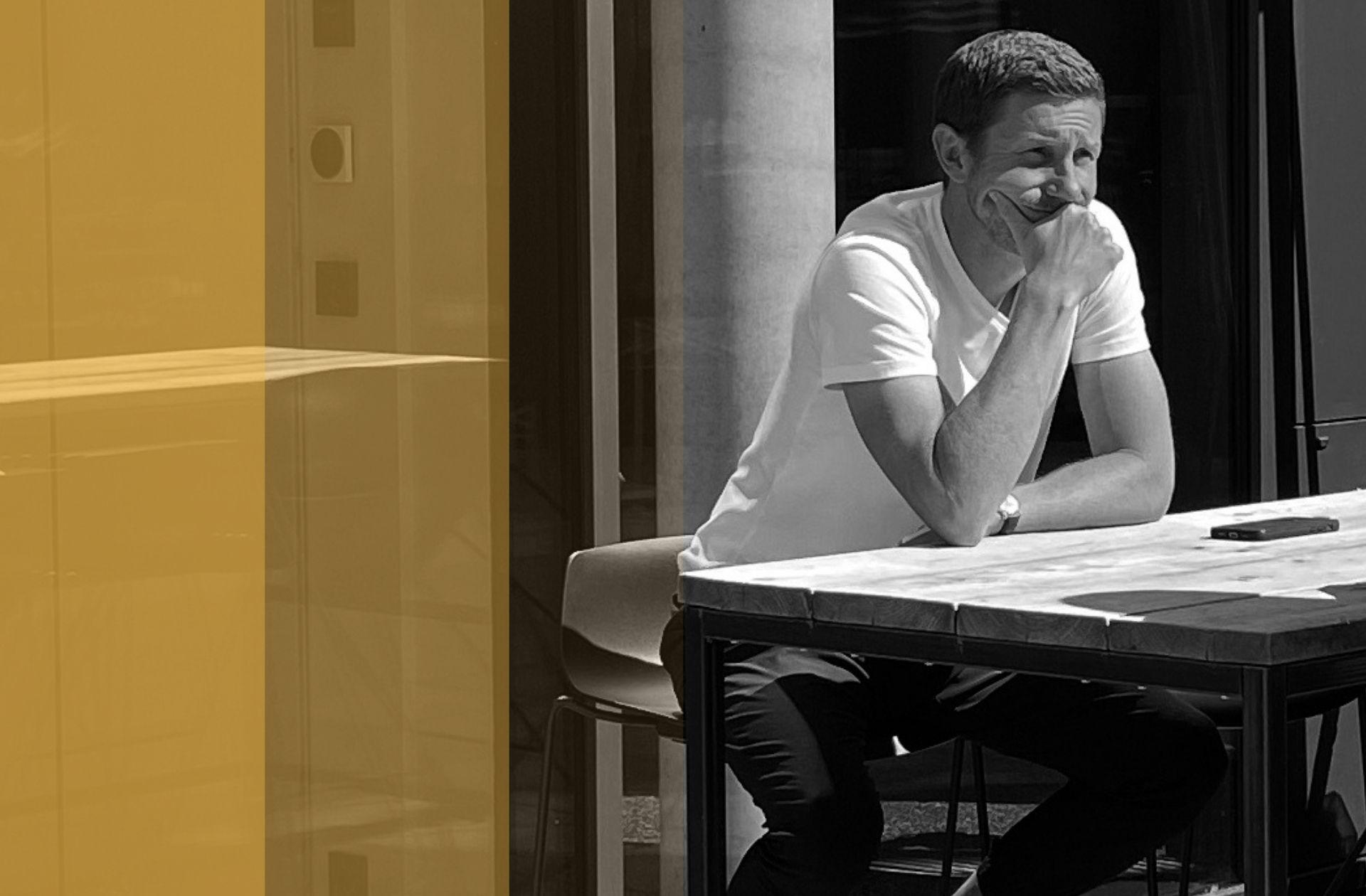Mark Poppenborg sitzt an einem Barhocker an einem Tisch und denkt nach.